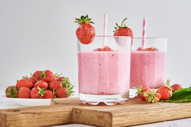 Strawberry milk shake in glass with straw and fresh berries on white background