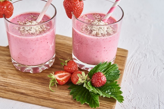 Strawberry milk shake in glass with straw and fresh berries