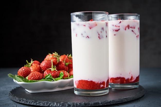 Strawberry milk smoothie in glass and fresh berries on dark background