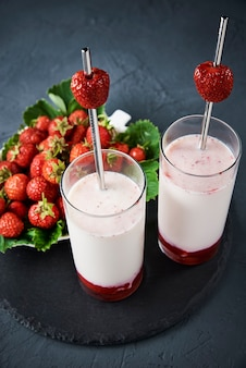 Strawberry milk smoothie in glass with straw and fresh berries on dark background