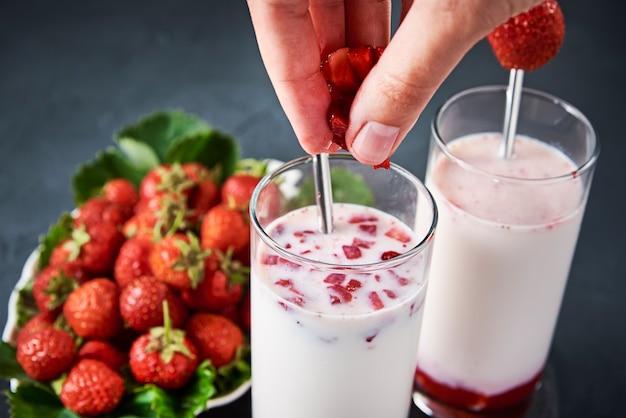 Strawberry milk smoothie in glass with straw