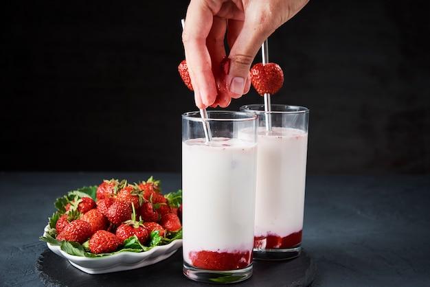 Клубничный молочный коктейль в стакане с соломой и свежими ягодами