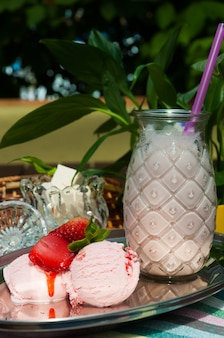 Strawberry milkshake in a glass glass with strawberries and marshmallows