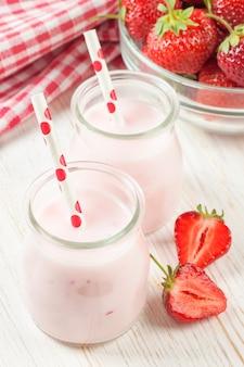 白い木製のテーブルの上のストローとガラスの瓶にイチゴのミルクセーキ