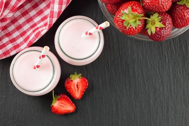 黒いスレートの表面にストローを入れたガラス瓶の中のイチゴのミルクセーキ。上面図