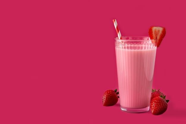 Клубничный молочный коктейль на розовом фоне