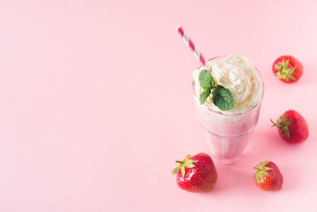 Strawberry milkshake or smoothie and fresh raw berries on pink