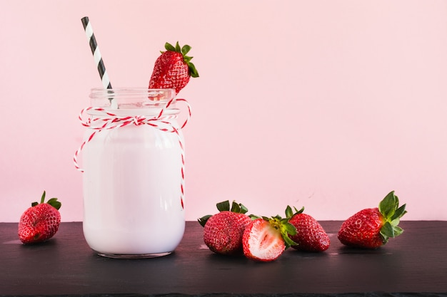 Strawberry milkshake with berry in mason jar on pink. close up. summer drink.
