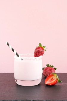 Strawberry milkshake with berry on pink. close up. summer food.