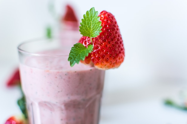 Strawberry milkshake with mint on a white background