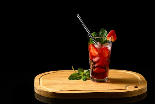 Клубничный коктейль мохито джин-тоник освежающий напиток клубника и ортелан на черном фоне
