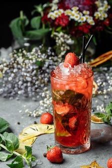 Клубничный мохито. холодный летний коктейль мохито с клубникой, мятой, лимоном и льдом в стакане на столе.