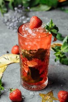 いちごモヒート。テーブルの上のグラスにイチゴ、ミント、レモン、氷と冷たい夏のモヒートカクテル。