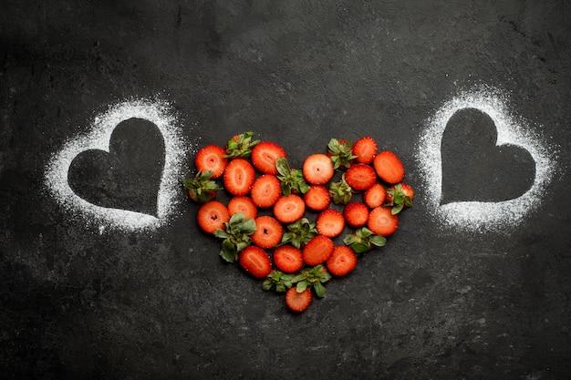Клубника на темном камне в форме сердца, символ любви ко дню всех влюбленных.