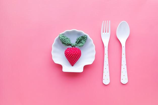 パステルカラーの背景を持つ皿にイチゴ。夏のコンセプトのアイデア
