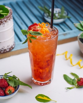 Strawberry and orange juice with ice cubes, orange zest, strawberry piece in glass