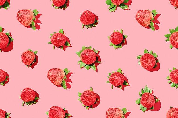 ピンクの背景にイチゴのパターン。ジューシーなイチゴ。上面図。