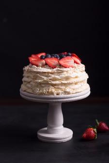 Strawberry pavlova cake on a black background and table