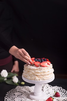 Strawberry pavlova cake decorated by woman. black background and copyspace