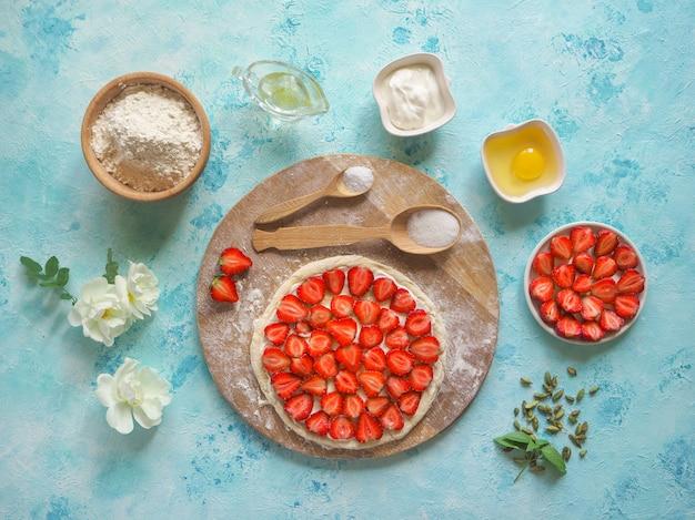 ストロベリーパイ。ターコイズブルーのキッチンテーブルにイチゴのパイを焼くための材料。