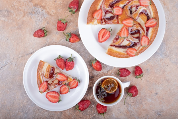 흰색 접시에 차 한잔과 딸기 파이