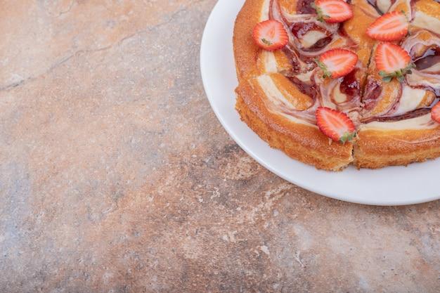 흰색 접시에 초콜릿 시럽을 곁들인 딸기 파이