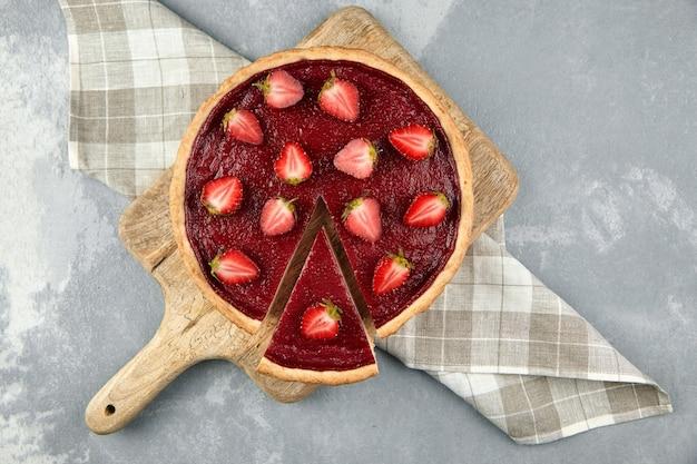 Клубничный пирог с половинками свежих ягод на сером каменном столе