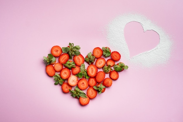 Strawberry on pink in the shape of a heart with powdered sugar, a symbol of love