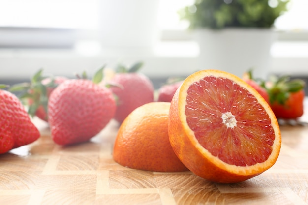 Strawberry and red orange on kitchen table