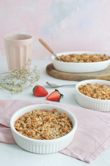 Strawberry and rhubarb homemade granola crumble with ice-cream top view on white concrete