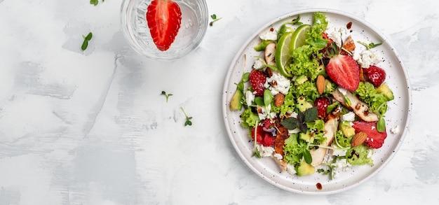 닭고기 아보카도, 페타 치즈, 양상추, 견과류 발사믹 식초를 곁들인 딸기 샐러드. 건강식 트렌드. 긴 배너 형식입니다. 평면도.