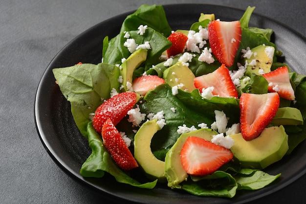 접시에 시금치, 페타 치즈, 아보카도, 발사믹 식초, 올리브 오일을 넣은 딸기 샐러드