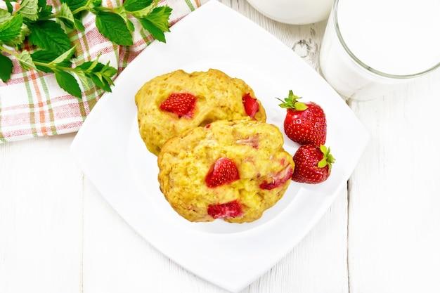 딸기, 냅킨, 민트, 주전자에 우유, 위의 나무 판자 배경에 유리가 있는 접시에 있는 딸기 스콘