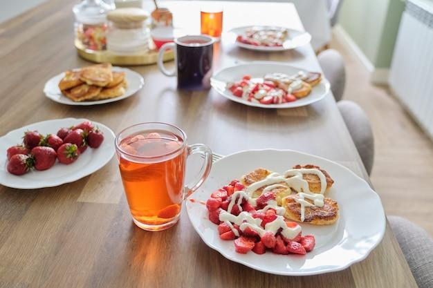 いちごの季節、ベリーと一緒に食べ物や飲み物。テーブルの上の食べ物、イチゴとサワークリームの豆腐パンケーキ。レモンとベリーのお茶