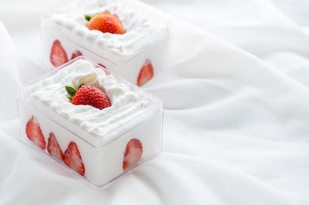 布の背景とコピースペース、最小限のケーキとパン屋のコンセプトでプラスチックの箱にストロベリーショートケーキ