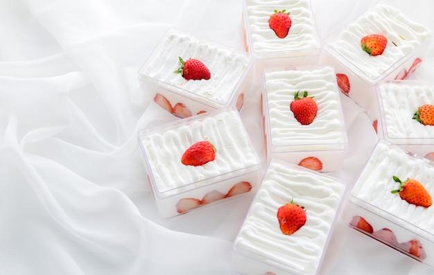 布の背景とコピースペース、最小限のケーキとパン屋のコンセプトとプラスチックの箱にイチゴのショートケーキ