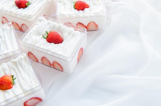 布の背景とコピースペースでプラスチックの箱にイチゴのショートケーキ