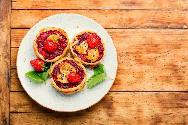 딸기 쇼트케이크 파이. 신선한 딸기를 곁들인 맛있는 타르트. 소박한 나무 배경에 달콤한 디저트