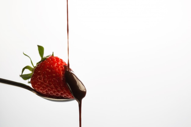 A strawberry sitting on a spoon gets chocolate syrup dropped on it.