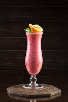 Strawberry smoothie on dark wood