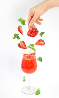 Strawberry smoothie and falling pieces of berries and sprigs of mint in a glass.