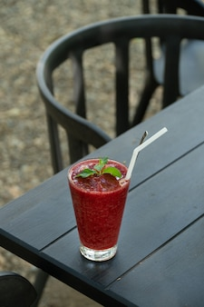 Strawberry smoothie frappe on black wood table.
