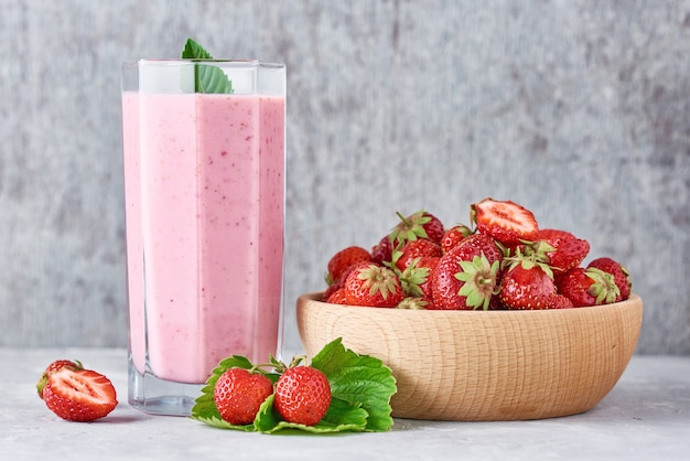 Strawberry smoothie in glass jar and fresh strawberries in wooden bowl on gray