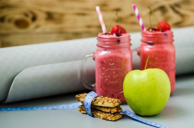 イチゴのスムージーやミルクセーキ、新鮮なイチゴ、サクランボ、木製の背景にクッキーとアップル