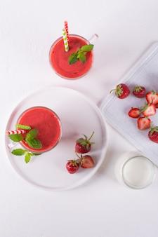 イチゴのスムージーまたはガラスのコップのミルクセーキ。朝食とスナックの健康食品。上面図