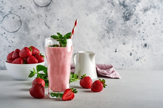 Клубничный коктейль или молочный коктейль с ягодами и мятой в высоком стакане на светло-сером фоне. летний коктейль, молочный коктейль и органическая концепция освежения. место для текста.