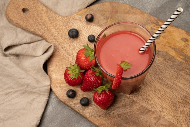 Strawberry smoothie strawberries and blueberries on wooden board