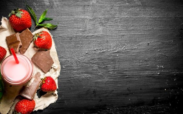 チョコレートとミントのストロベリースムージー。黒い木製のテーブルの上。