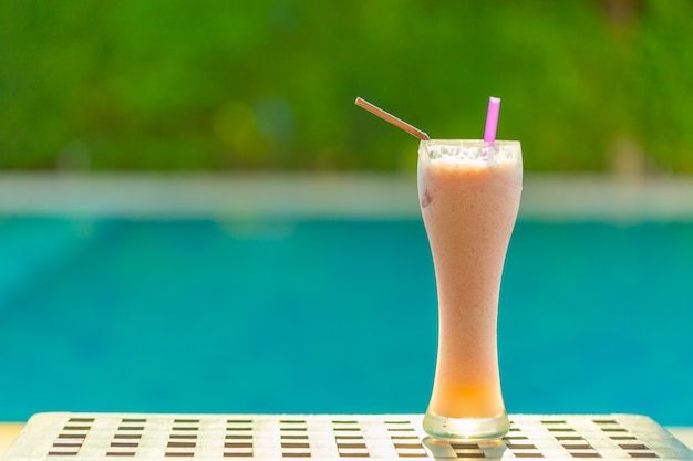 Strawberry smoothie on wooden table near by swiming pool with copy space