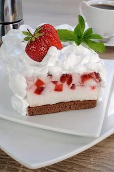 생크림을 곁들인 초콜릿 스폰지 케이크에 딸기 수플레